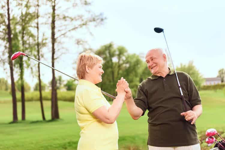 Senior couple celebrates during a round of golf.